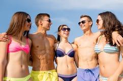 Усмехаясь друзья в солнечных очках на пляже лета Стоковые Фотографии RF