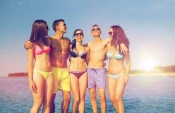 Усмехаясь друзья в солнечных очках на пляже лета Стоковая Фотография