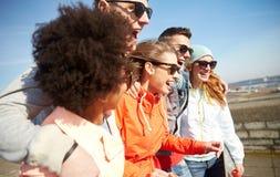Усмехаясь друзья в солнечных очках смеясь над на улице Стоковые Фото