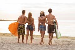 Усмехаясь друзья в солнечных очках с прибоями на пляже Стоковая Фотография