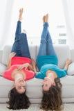 Усмехаясь друзья лежа на софе с ногами в воздухе дома Стоковые Фото