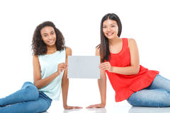 Усмехаясь друзья держа лист бумаги Стоковые Изображения