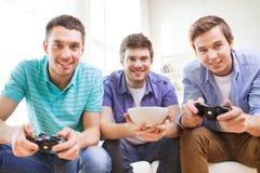 Усмехаясь друзья играя видеоигры дома Стоковое Фото