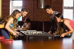 Усмехаясь друзья играя футбол таблицы Стоковые Изображения RF