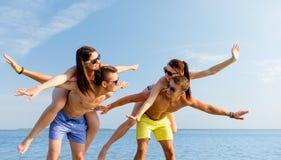 Усмехаясь друзья имея потеху на пляже лета Стоковое фото RF