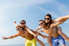 Усмехаясь друзья имея потеху на пляже лета Стоковая Фотография