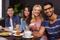 Усмехаясь друзья наслаждаясь кофе совместно и использованием технологий Стоковое фото RF