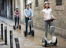 Усмехаясь друзья представляя на segways на улице города Стоковая Фотография