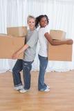 Усмехаясь друзья стоя спина к спине держащ moving коробки Стоковая Фотография RF