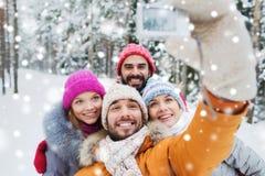 Усмехаясь друзья с камерой в лесе зимы Стоковые Изображения