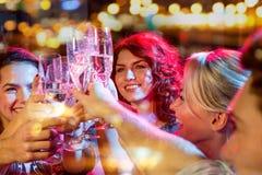 Усмехаясь друзья с стеклами шампанского в клубе Стоковые Изображения