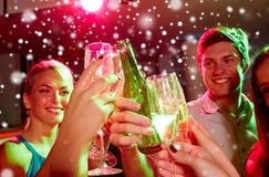 Усмехаясь друзья с стеклами шампанского в клубе Стоковые Изображения RF