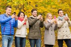 Усмехаясь друзья с smartphones в парке города Стоковое Изображение