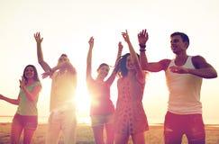Усмехаясь друзья танцуя на пляже лета Стоковая Фотография