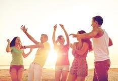 Усмехаясь друзья танцуя на пляже лета Стоковое Изображение