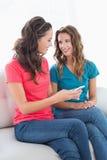 Усмехаясь друзья читая текстовое сообщение дома Стоковое Фото