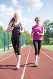 Усмехаясь друзья Jogging на следе совместно Стоковая Фотография