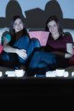 2 усмехаясь друз на кресле смотря ТВ совместно в dar Стоковое фото RF