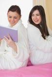2 усмехаясь друз нося купальные халаты сидя спина к спине looki Стоковые Изображения RF