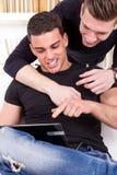 2 усмехаясь друз указывая пальцы на компьтер-книжку Стоковые Фото