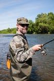 Усмехаясь рыболов на реке стоковое изображение rf