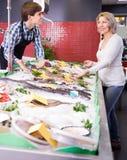Усмехаясь рыбы продавца предлагая для того чтобы созреть клиент в магазине стоковая фотография rf