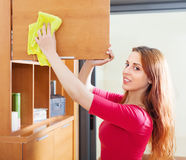 Усмехаясь рыжеволосая женщина очищая деревянное furiture Стоковое Изображение RF