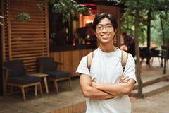 Усмехаясь рюкзак азиатского человека студента нося стоковые фотографии rf