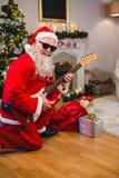 Усмехаясь Санта Клаус играя гитару Стоковое Фото