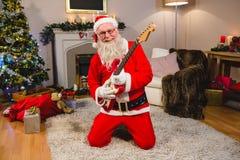 Усмехаясь Санта Клаус играя гитару Стоковое Изображение