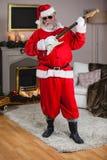 Усмехаясь Санта Клаус играя гитару Стоковые Фотографии RF