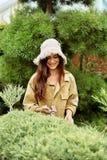 Усмехаясь садовник девушки в одеждах и соломенной шляпе деятельности стоковое фото
