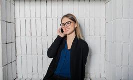 Усмехаясь секретарша женщины в стеклах говоря на мобильном телефоне во время пролома работы в компании Стоковые Изображения RF