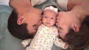 Усмехаясь семья в кровати, где крутой план стороны папа, мама и маленькая дочь, родители нежно поцеловать их младенца сток-видео