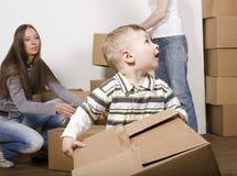 Усмехаясь семья в новом доме играя с коробками Стоковое Фото