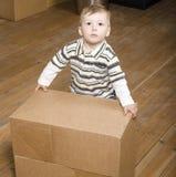 Усмехаясь семья в новом доме играя с коробками Стоковые Фото