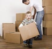Усмехаясь семья в новом доме играя с коробками Стоковое Изображение RF