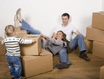 Усмехаясь семья в новом доме играя с коробками Стоковая Фотография