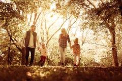 Усмехаясь семья в парке совместно Стоковое Изображение RF