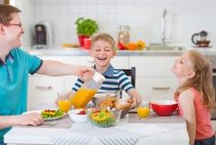 Усмехаясь семья есть завтрак в кухне Стоковые Фотографии RF