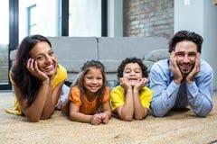 Усмехаясь семья на ковре в живущей комнате Стоковое Изображение