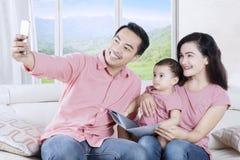 Усмехаясь семья принимая фото selfie на софе стоковая фотография