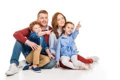 усмехаясь семья при 2 дет указывая прочь с пальцами Стоковая Фотография RF