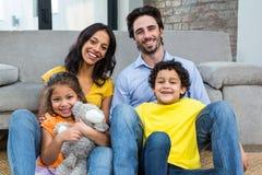 Усмехаясь семья сидя на ковре в живущей комнате Стоковая Фотография RF