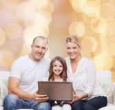 Усмехаясь семья с компьтер-книжкой Стоковая Фотография RF