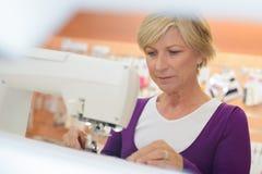 Усмехаясь середина постарела женщина используя швейную машину в прачечной стоковое изображение rf