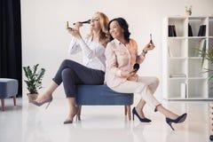 Усмехаясь середина постарела коммерсантки сидя совместно и прикладывать состав в офисе Стоковые Фото