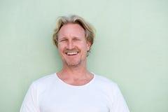 Усмехаясь середина постарела человек стоя против зеленой предпосылки Стоковое Фото