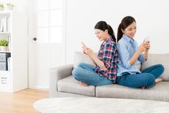 Усмехаясь сестры спина к спине сидя на софе Стоковая Фотография RF