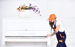 Усмехаясь сильный человек с стильной бородой и усик пробуя двинуть старый деревянный рояль с вазой цветка Красивый работник внутр Стоковое Изображение